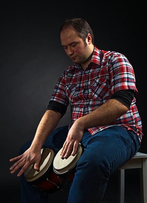 Ein Musiker spielt sitzend Bongo-Trommeln. Die Bongos hält er traditionell zwischen den Beinen.